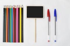 Hölzerne Bleistifte als Nächstes und Stift zwei zur kleinen quadratischen Tafel auf weißem Hintergrund Lizenzfreies Stockfoto