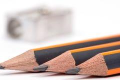 Hölzerne Bleistifte mit Metallbleistiftspitzer über Weißrückseite Lizenzfreie Stockfotografie