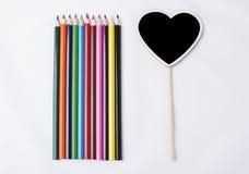 Hölzerne Bleistifte nahe bei kleiner Tafel mit Herzen formen auf weißen Hintergrund Stockfoto