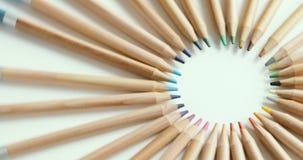 Hölzerne Bleistifte von verschiedenen Farben werden in Kreis auf weißer Oberfläche, bunte Kunst, helles Rot, Grün, Gelb, Rosa ein stock video footage