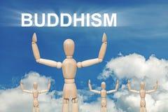 Hölzerne blinde Marionette auf Himmelhintergrund mit Text BUDDISM Stockfoto