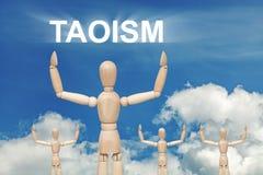 Hölzerne blinde Marionette auf Himmelhintergrund mit Text TAOISMUS Stockfoto