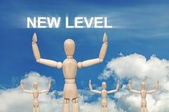 Hölzerne blinde Marionette auf Himmelhintergrund mit Wörter NEUEM NIVEAU Lizenzfreie Stockfotos