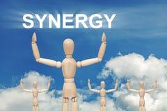 Hölzerne blinde Marionette auf Himmelhintergrund mit Wort SYNERGIE Lizenzfreies Stockbild