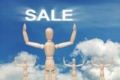 Hölzerne blinde Marionette auf Himmelhintergrund mit Wort VERKAUF Stockfotografie