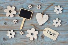 Hölzerne Blumen und Herz auf einem alten hölzernen Hintergrund mit danken für Sie Aufkleber und und schwarzem leerem Raumplan des Lizenzfreies Stockbild