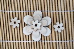 Hölzerne Blumendekoration auf einem Reedhintergrund Stockbilder