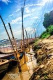 Hölzerne Boote parkten im Wasser mit bewölktem Himmel und Sonnenstrahlen Lizenzfreie Stockbilder