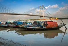 Hölzerne Boote richteten auf Fluss Hooghly bei Princep Ghat mit Vidyasagar-Brücke u. x28 aus; setu& x29; am Hintergrund Stockbilder