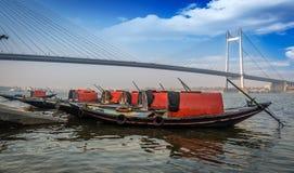 Hölzerne Boote richteten auf Hooghly-Flussbank aus, die Vidyasagar-Brücke Setu übersieht Stockfotografie