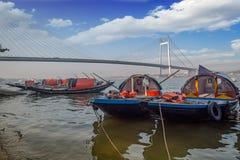 Hölzerne Boote richteten auf Hooghly-Flussbank mit Vidyasagar-Brücke Setu am Hintergrund aus Stockfotos