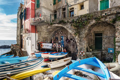 Hölzerne Boote werden an der Küste von Riomaggiore-Stadt in Cinque Terre National-Park, Italien festgemacht Lizenzfreie Stockbilder
