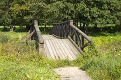 Hölzerne Brücke über kleinem Fluss im grünen Park. Lizenzfreies Stockfoto