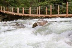 Hölzerne Brücke über wildem Wasser Lizenzfreies Stockfoto