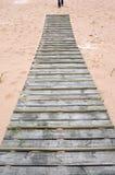 Hölzerne Brücke auf Sand im Seestrand Stockbild
