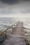 Hölzerne Brücke auf wellenförmigem See. Dunkler Himmel vor Sturm stockbilder