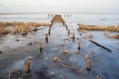 Hölzerne Brücke in gefrorenem See Stockbilder