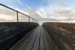 Hölzerne Brücke mit Wolken und Himmel oben Lizenzfreie Stockfotografie