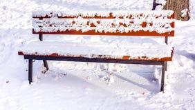 Hölzerne braune Bank mit Schnee auf ihm gegen Schneeteppich im Sonnenschein Bänke im Winterstadtpark, der gewesen ist Stockbilder