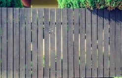 Hölzerne braune Hecke mit Grün bepflanzt Thuja an der Spitze mit Büschen lizenzfreie stockbilder