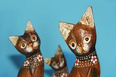 hölzerne braune Katzenandenken sitzen auf einem blauen Hintergrund lizenzfreies stockbild