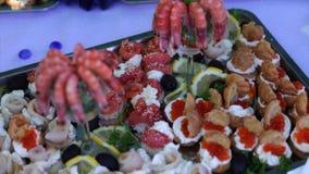 Hölzerne braune Tabellen voll von verschiedenen Snäcken für Partei- oder Hochzeitsfeier stock footage