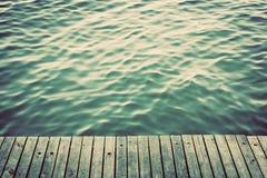 Hölzerne Bretter des Schmutzes eines Piers über Ozean mit dem Plätschern bewegt wellenartig weinlese Stockfotos
