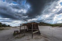 Hölzerne Bretterbude mit drastischen Wolken und Sonnenstrahl im Hintergrund lizenzfreie stockbilder