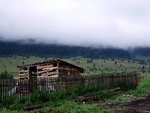 Hölzerne Bretterbude unter nebelhaftem Berg Stockbild