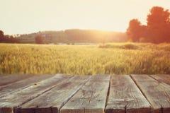 Hölzerne Bretttabelle vor Feld des Weizens auf Sonnenunterganglicht Bereiten Sie für Produktanzeigenmontagen vor stockfotografie