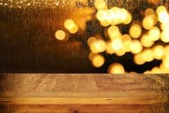 Hölzerne Bretttabelle vor Weihnachtswarmer Goldgirlande beleuchtet auf hölzernem rustikalem Hintergrund lizenzfreie stockfotografie