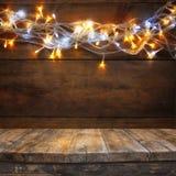 Hölzerne Bretttabelle vor Weihnachtswarmer Goldgirlande beleuchtet auf hölzernem rustikalem Hintergrund Gefiltertes Bild Selektiv Stockfotografie