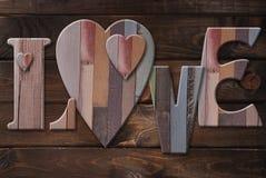 Hölzerne Buchstabeliebe mit Herzen Stockbilder