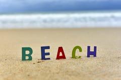 Hölzerne Buchstaben des STRANDES auf dem Strand Lizenzfreies Stockbild