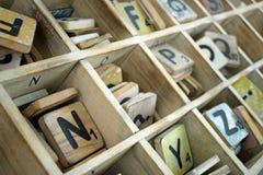Hölzerne Buchstaben mit Zahlen in einem hölzernen Behälter Stockfotos