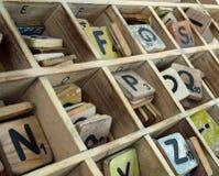 Hölzerne Buchstaben mit Zahlen in einem hölzernen Behälter Stockfotografie