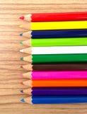 Hölzerne bunte Bleistifte mit dem Schärfen von Schnitzeln, auf Holztisch Lizenzfreie Stockfotos