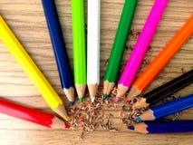 Hölzerne bunte Bleistifte mit dem Schärfen von Schnitzeln, auf Holztisch Stockfotos