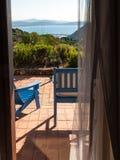 Hölzerne deckchairs auf dem Patio vor dem Meer Stockbilder