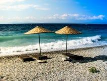 Hölzerne deckchairs unter Regenschirmen auf Strand lizenzfreie stockfotos