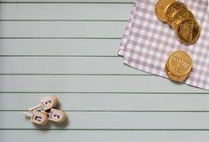 Hölzerne dreidels für Chanukka-Kreisel- und -schokoladenmünzen lizenzfreie stockfotos