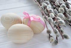 Hölzerne Eier mit bunten Bändern mit dem Zweig der Pussyweide auf whi Stockfoto