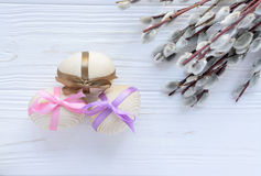 Hölzerne Eier mit bunten Bändern mit Zweig Pussyweide auf whi Stockfoto