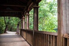 Hölzerne eingezäunte Brücke und entfernte Bahn Stockbild