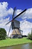 Hölzerne Entwässerungswindmühle in einem Polder mit einem blauen Himmel und drastischen Wolken, die Niederlande Lizenzfreie Stockfotos