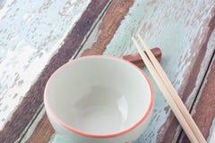 Hölzerne Essstäbchen und leere Schüssel auf hölzernem Hintergrund Stockfotografie