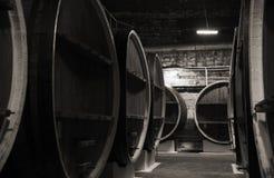 Hölzerne Fässer der Weinlese in der dunklen Weinkellerei Stockbild