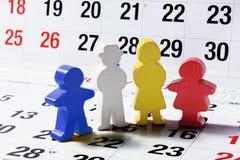 Hölzerne Familien-Abbildungen auf Kalender-Seite stockbild