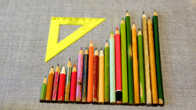 Hölzerne farbige Bleistifte und dreieckiger Machthaber Stockfotografie