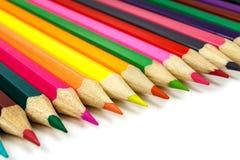 Hölzerne farbige Bleistifte vereinbarten in Folge auf einem weißen Hintergrund Lizenzfreies Stockbild